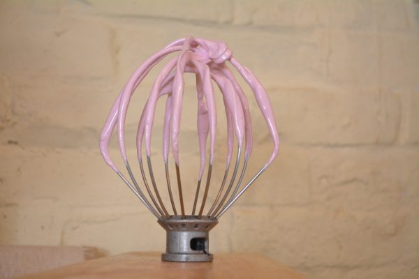 A wire whisk coated with purple marshmallow mix standing upright against a plain background