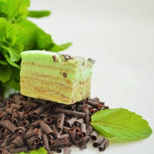 Pale green chocolate mint marshmallow sitting on pile of chocolate curls and decorated with mint leaves