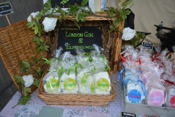 A wicker basket containing bags of elderflower and gin marshmallows, draped with a garland of ivy leaves and white roses