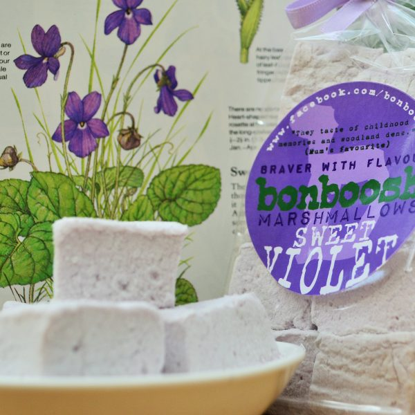 Three lilac colored marshmallows in a small white dish in front of an open book with illustration of violets. To the right of the image is a full pack of marshmallows