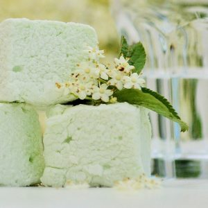 Three soft green marshmallows and a sprig of elderflower and leaves, with a glass of gin in the background