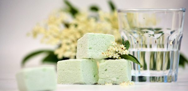 Three pale green marshmallows decorated with a sprig of elderflowers next to a clear small glass of gin, blurred for effect