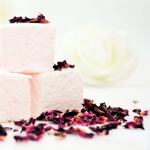 Three pale pink marshmallows sprinkled with dried red rose petals