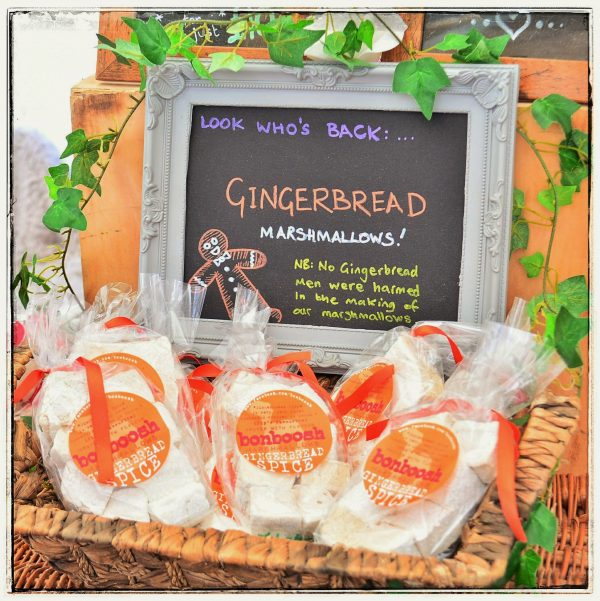 Wicker basket containing bags of gingerbread spice marshmallows, with orange labels and ribbons. Behind the marshmallows is a framed chalkboard sign explaining that no gingerbread men were harmed in the making of the marshmallows.