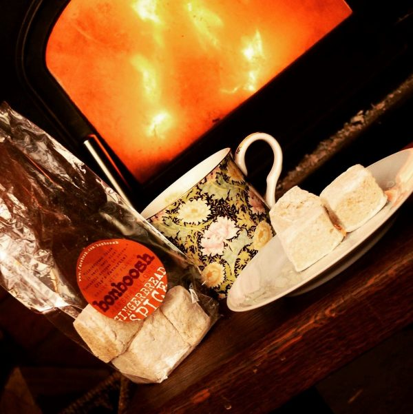 Opened pack of marshmallows on a table with a plate holing two marshmallows and a china floral mug. Logburning fire in the background to create a cosy image.
