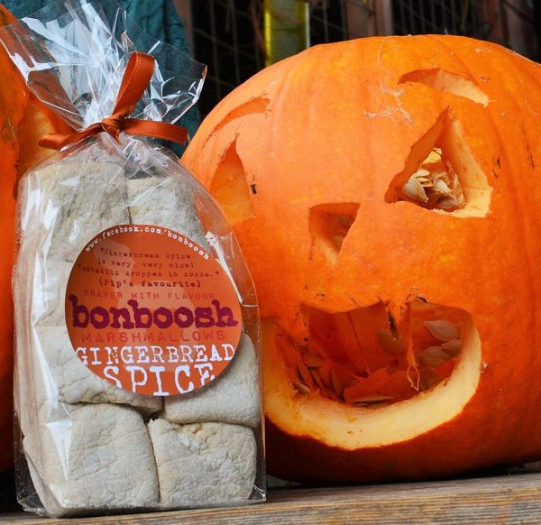 A pack of gingerbread spice marshmallows pictured next to a carved pumpkin face