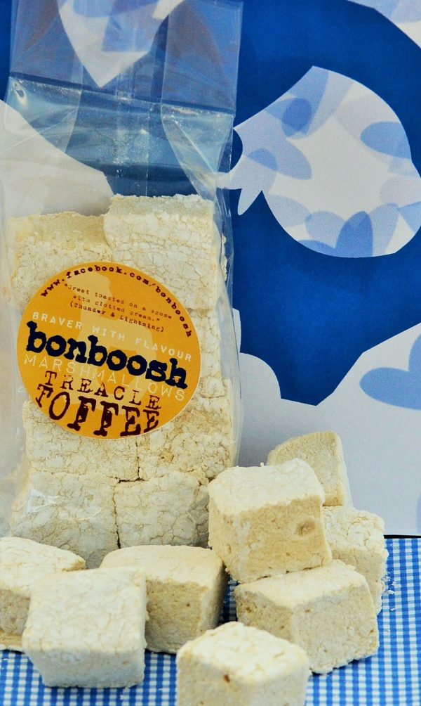 An eight piece bag of treacle toffee marshmallows with loose marshmallows scattered around, on a blue gingham cloth, against a blue and white background