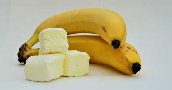 Three pale yellow marshmallows stacked in front of two bananas