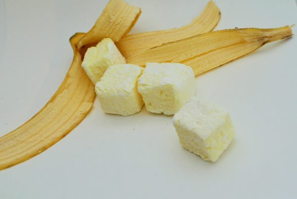 Four pale yellow marshmallows spilling from an opened banana skin