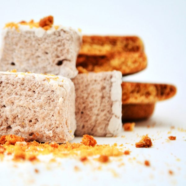 Three marshmallows stacked in front of a pile of gingerbread, scattered with gingerbread crumbs
