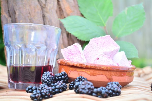 A terracotta bowl containing purple marshmallows, with blackberries in the foreground. a glass of sloe gin and bramble leaves in the background
