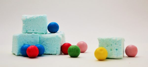 Pale blue marshmallows surrounded by multi coloured gum balls, set against a white background