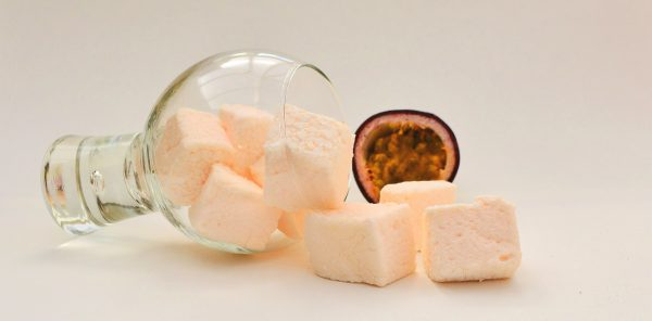 A gin glass laying on it's side with marshmallows spilling out, half a passion fruit in the background