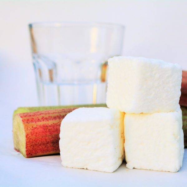 Three bonboosh marshmallows sitting alongside two pieces of rhubarb, with a glass of gin in the background
