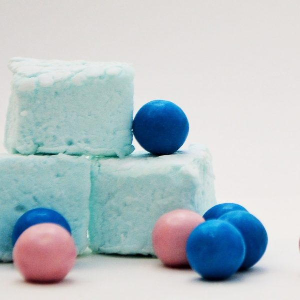 Three pale blue marshmallows surrounded by blue and pink gum balls, set against a white background