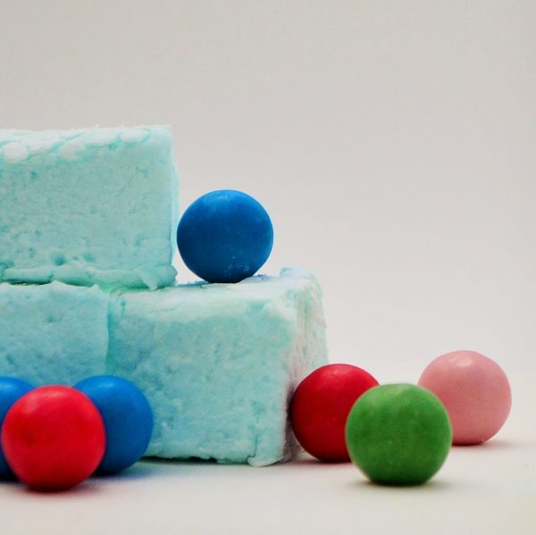 Three pale blue marshmallows surrounded by multi coloured gum balls, set against a white background