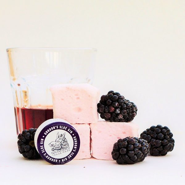 Three pale mauve marshmallows surrounded by fresh blackberries, in front of a glass of sloe gin. A Sloe Gin bottle top rests in front of the marshmallows