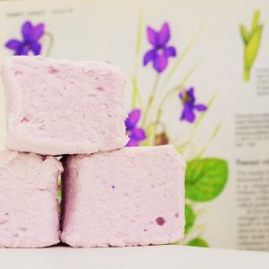 three pale violet bonboosh marshmallows stacked in front of an open book showing an illustration of violet flowers