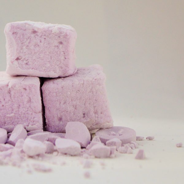 Three pale violet bonboosh marshmallows sitting on top of a scattering of crushed parma violet sweets