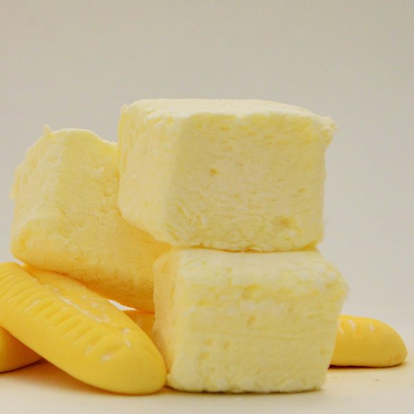 Three pale yellow marshmallows stacked on top of two foam banana sweets against a plain white background.