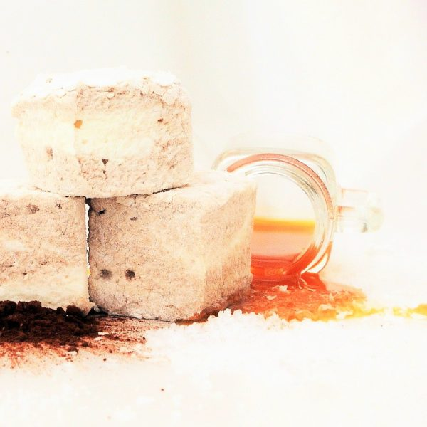 Three brown and cream marbled bonboosh marshmallows sat atop a scattering of cocoa powder and sea salt, alongside a glass spilling a puddle of caramel sauce