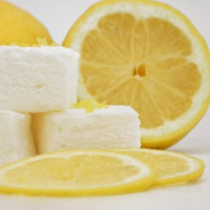 Three white marshmallows stacked in front of a half lemon, with two lemon slices laid in front of them. Grated lemon zest is sprinkled on the marshmallows.