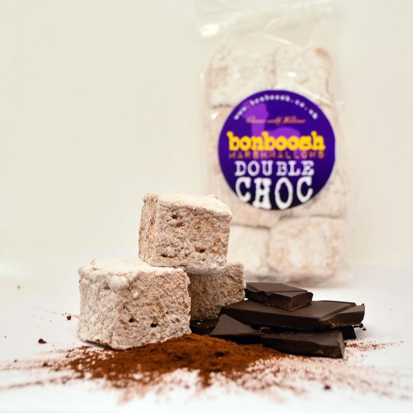 Three square cut bonboosh marshmallows sat on top of a scattering of cocoa powder, with pieces of dark chocolate stacked alongside. A bag of bonboosh marshmallows can be seen in the background.