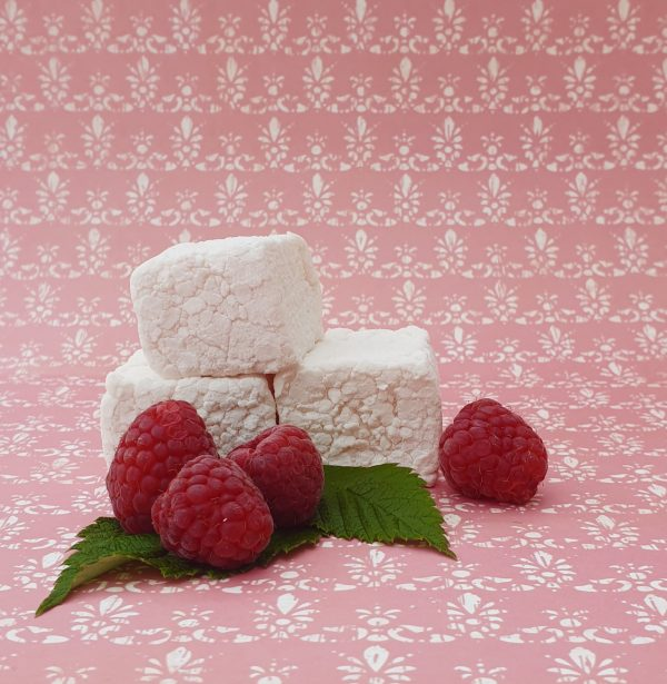A stack of three bonboosh marshmallows against a patterned pink backdrop surrounded by fresh raspberries and green leaves