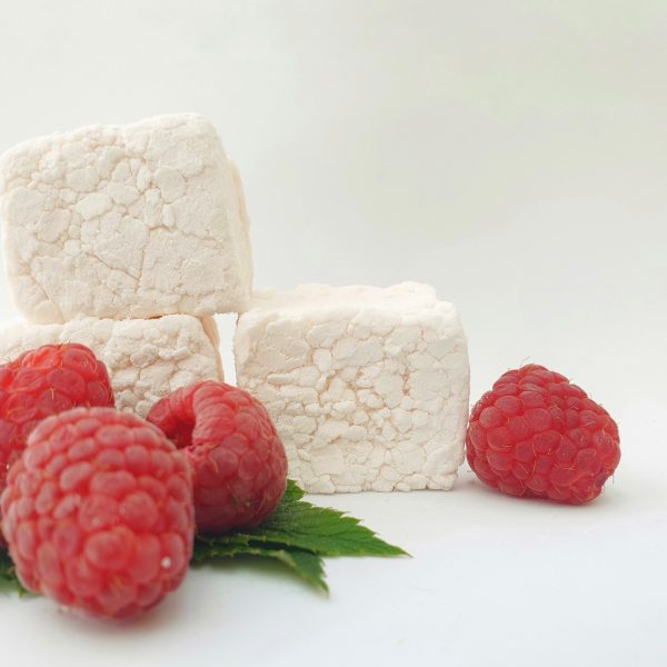 Three bonboosh marshmallows stacked on top of each other against a plain white background surrounded by fresh raspberries and green leaves