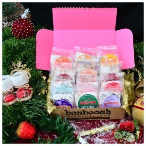 Pink postal box containing a selection of 4 piece pack marshmallows in a christmas greenery setting